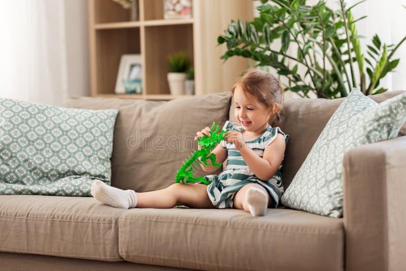 Ευτυχές παιχνίδι κοριτσάκι με το δεινόσαυρο παιχνιδιών στο σπίτι στοκ φωτογραφία με δικαίωμα ελεύθερης χρήσης