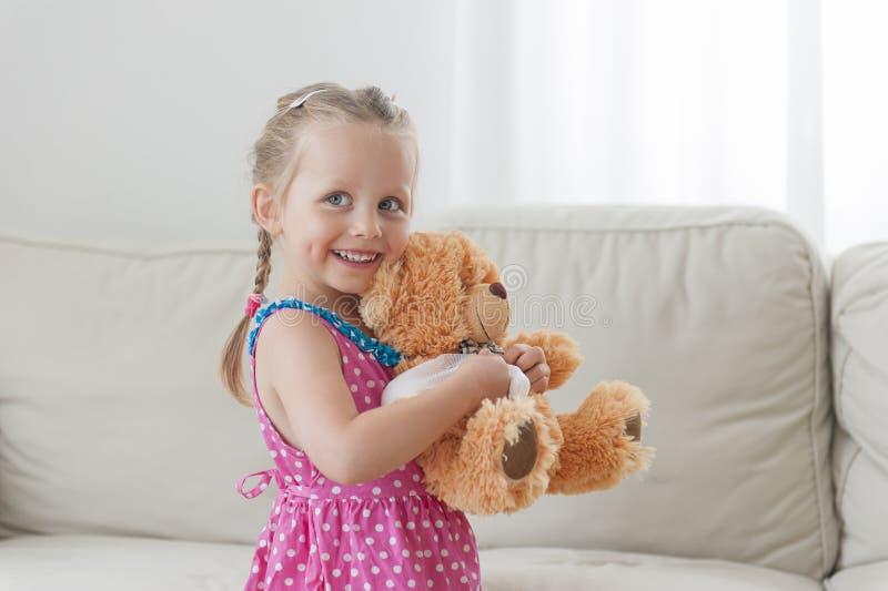 Ευτυχές παιχνίδι κοριτσιών μικρών παιδιών με τη teddy αρκούδα της στο σπίτι στοκ φωτογραφία με δικαίωμα ελεύθερης χρήσης