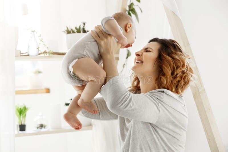 Ευτυχές παιχνίδι μητέρων χαμόγελου με το νεογέννητο παιδί στη comfy ελαφριά κρεβατοκάμαρα μπροστά από το παράθυρο Στιγμές της μητ στοκ εικόνα