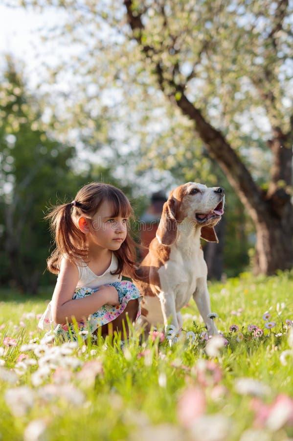 Ευτυχές παιχνίδι μικρών κοριτσιών με το σκυλί στον κήπο στοκ εικόνες με δικαίωμα ελεύθερης χρήσης