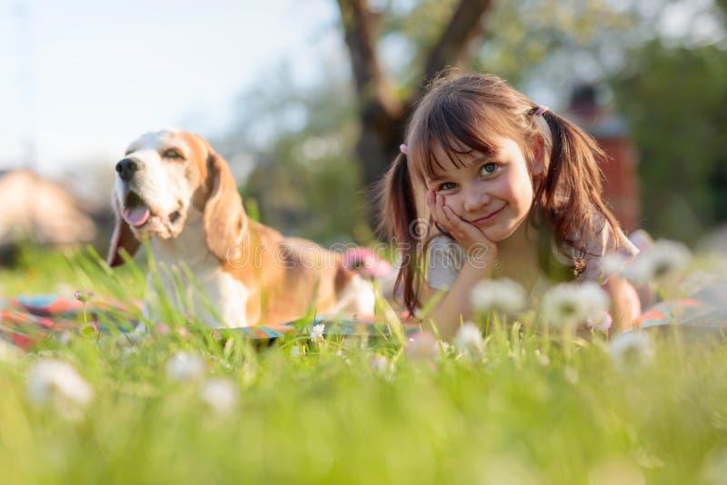 Ευτυχές παιχνίδι μικρών κοριτσιών με το σκυλί στον κήπο στοκ εικόνες