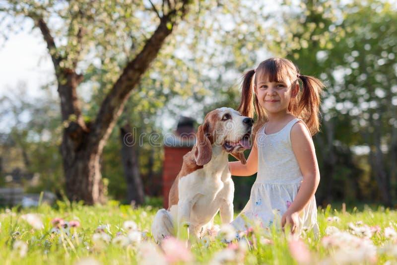 Ευτυχές παιχνίδι μικρών κοριτσιών με το σκυλί στον κήπο στοκ φωτογραφίες