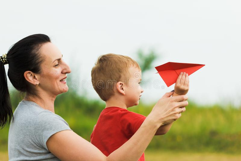 Ευτυχές παιχνίδι παιδιών με το αεροπλάνο εγγράφου μητέρων και παιχνιδιών ενάντια στο θερινό ουρανό στοκ φωτογραφίες με δικαίωμα ελεύθερης χρήσης
