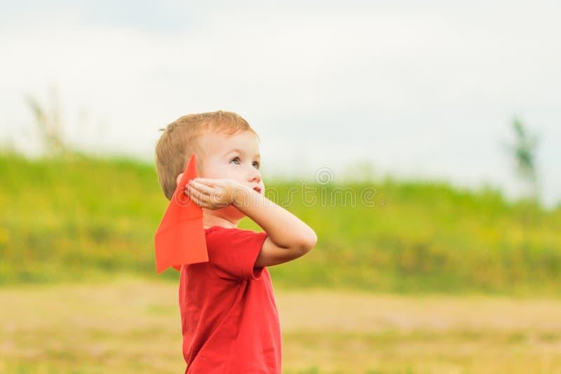 Ευτυχές παιχνίδι παιδιών με το αεροπλάνο εγγράφου παιχνιδιών ενάντια στο θερινό ουρανό στοκ φωτογραφία με δικαίωμα ελεύθερης χρήσης