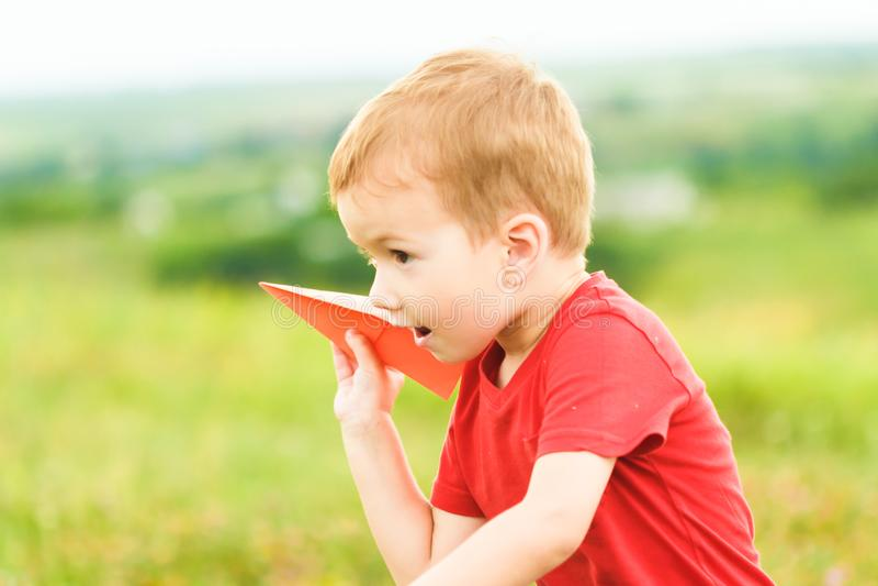 Ευτυχές παιχνίδι παιδιών με το αεροπλάνο εγγράφου παιχνιδιών ενάντια στο θερινό ουρανό στοκ φωτογραφία