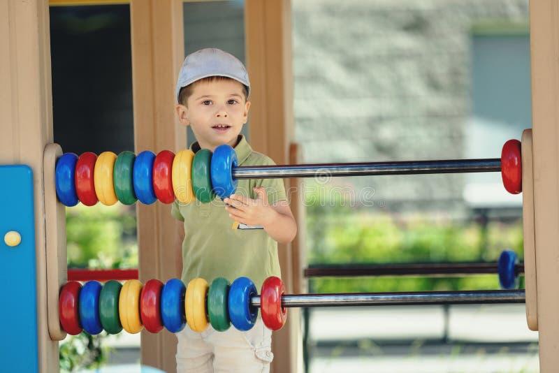 Ευτυχές παιχνίδι παιδιών σε μια παιδική χαρά Πορτρέτο ενός χαμογελώντας παιδιού στοκ φωτογραφία με δικαίωμα ελεύθερης χρήσης
