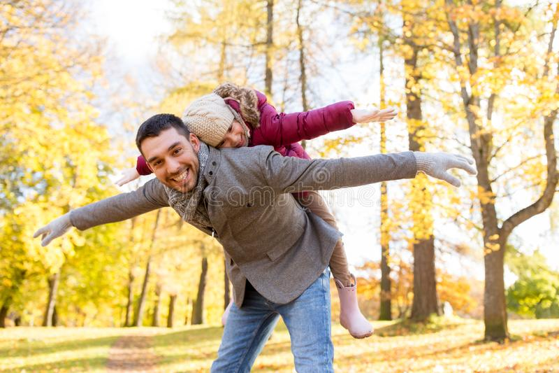 Ευτυχές παιχνίδι πατέρων και κορών στο πάρκο φθινοπώρου στοκ φωτογραφίες
