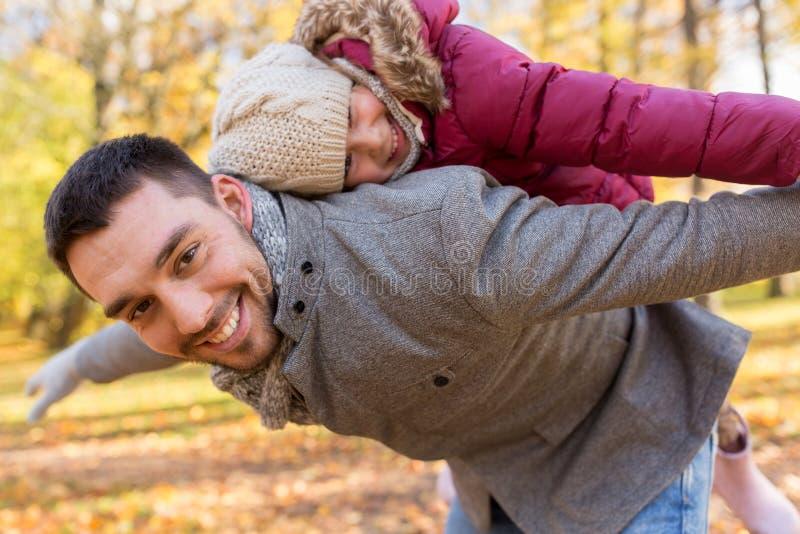 Ευτυχές παιχνίδι πατέρων και κορών στο πάρκο φθινοπώρου στοκ εικόνα