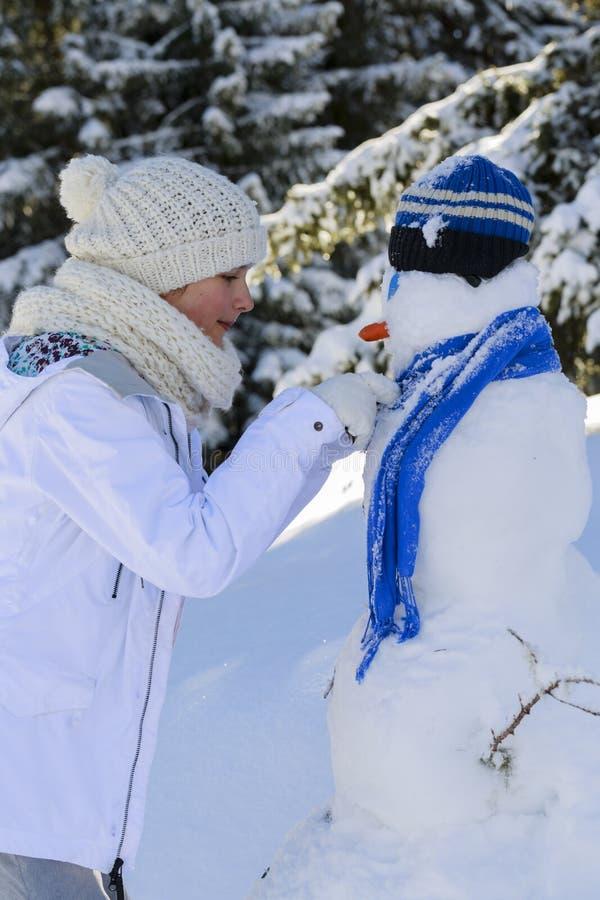 Ευτυχές παιχνίδι έφηβη χαμόγελου με έναν χιονάνθρωπο στοκ εικόνες με δικαίωμα ελεύθερης χρήσης