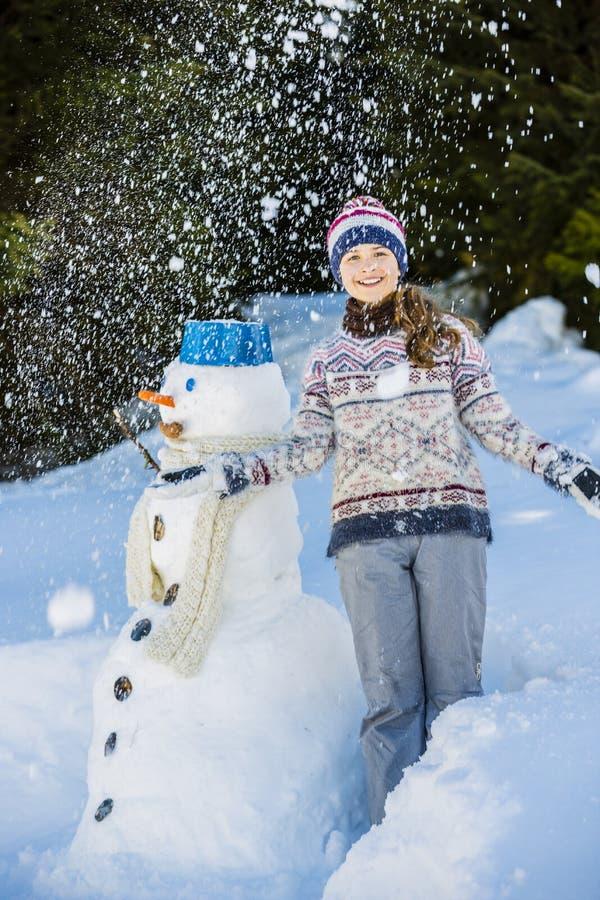 Ευτυχές παιχνίδι έφηβη χαμόγελου με έναν χιονάνθρωπο στοκ φωτογραφία