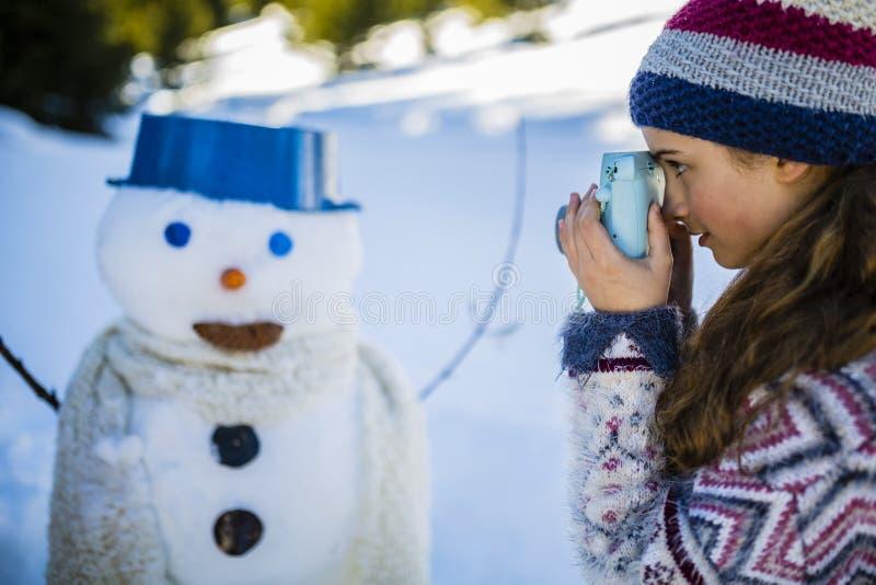 Ευτυχές παιχνίδι έφηβη χαμόγελου με έναν χιονάνθρωπο στοκ φωτογραφία με δικαίωμα ελεύθερης χρήσης