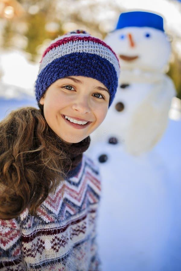 Ευτυχές παιχνίδι έφηβη χαμόγελου με έναν χιονάνθρωπο στοκ εικόνα με δικαίωμα ελεύθερης χρήσης