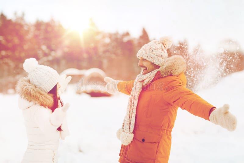 Ευτυχές παιχνίδι ζευγών με το χιόνι το χειμώνα στοκ εικόνα