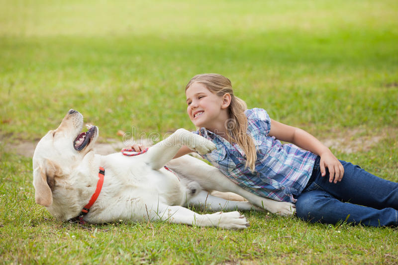 Ευτυχές παιχνίδι κοριτσιών με το σκυλί κατοικίδιων ζώων στο πάρκο στοκ φωτογραφία