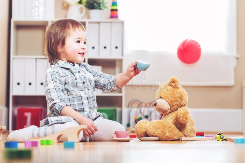 Ευτυχές παιχνίδι κοριτσιών μικρών παιδιών με τη teddy αρκούδα της στοκ εικόνα