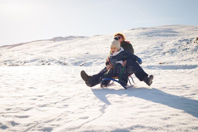 Ευτυχές παιχνίδι μητέρων και παιδιών στο χιόνι με ένα έλκηθρο στοκ εικόνα με δικαίωμα ελεύθερης χρήσης