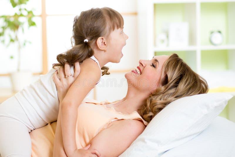 Ευτυχές παιχνίδι μητέρων με το παιδί της στο κρεβάτι στοκ φωτογραφίες