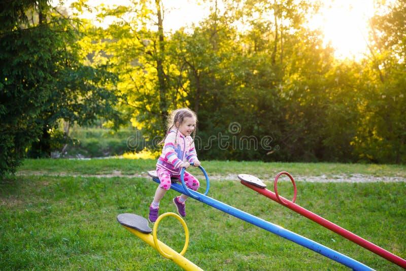 Ευτυχές παιχνίδι μικρών κοριτσιών, να ανεβεί αγγελία κάτω seesaw στοκ εικόνες