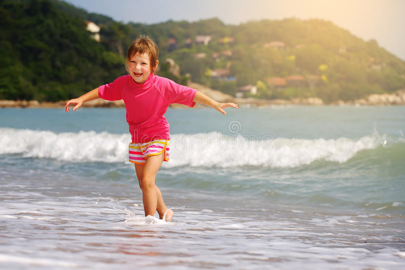 Ευτυχές παιχνίδι παιδιών στη θάλασσα στοκ εικόνα