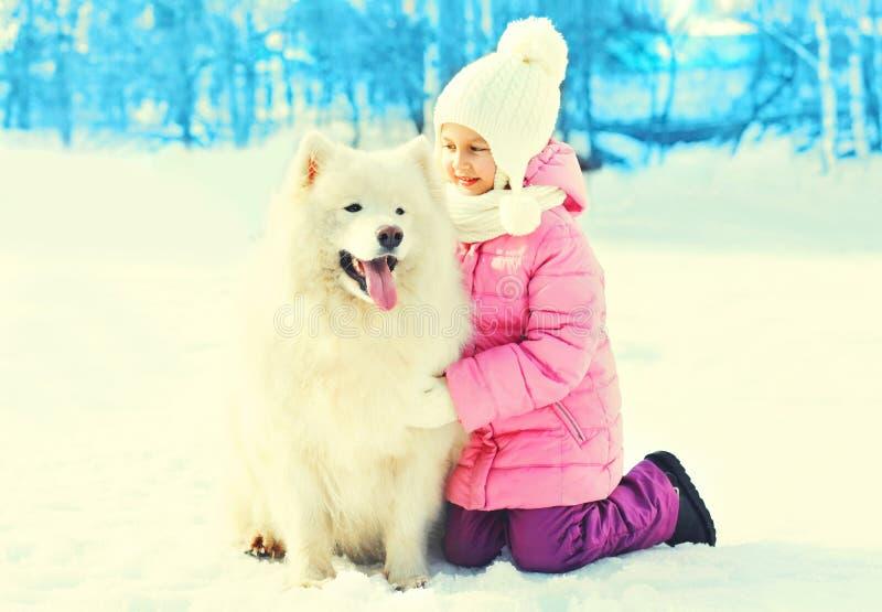 Ευτυχές παιδί με τον άσπρο χειμώνα σκυλιών Samoyed στοκ εικόνα