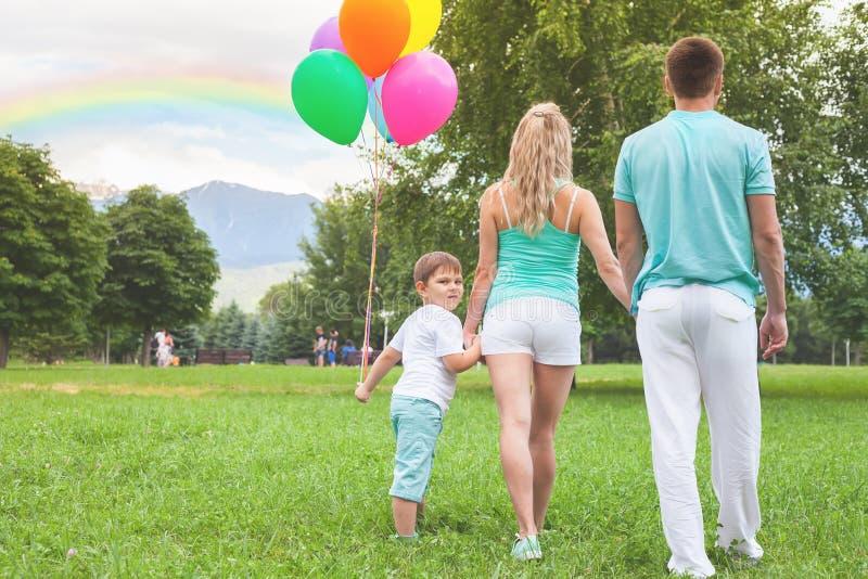Ευτυχές παιδί με τους γονείς mom, πατέρας που περπατά στο πάρκο Οικογένεια στοκ εικόνες