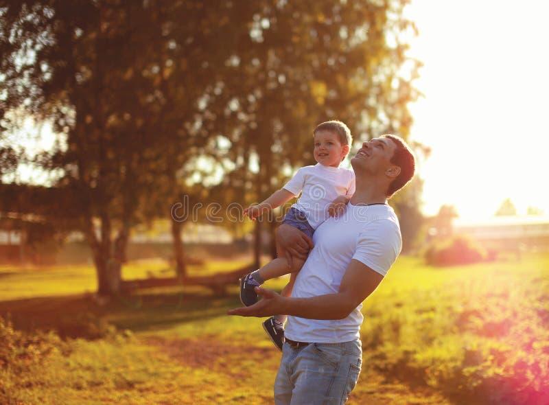 Ευτυχές παιδί πατέρων και γιων που έχει τη διασκέδαση μαζί, που απολαμβάνει το ηλιόλουστο φως του ήλιου θερινού βραδιού στο ηλιοβ στοκ φωτογραφία με δικαίωμα ελεύθερης χρήσης