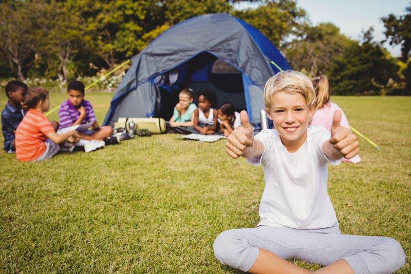 Ευτυχές παιδί που κάνει τους αντίχειρες επάνω κατά τη διάρκεια μιας ηλιόλουστης ημέρας στοκ φωτογραφία με δικαίωμα ελεύθερης χρήσης