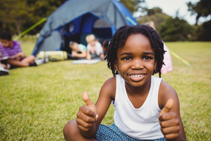Ευτυχές παιδί που κάνει τους αντίχειρες επάνω κατά τη διάρκεια μιας ηλιόλουστης ημέρας στοκ φωτογραφία