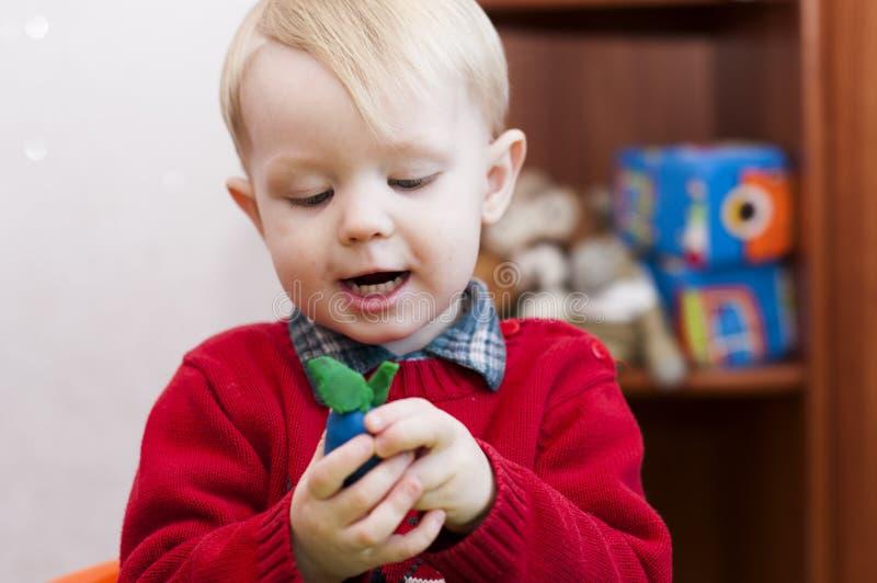 Ευτυχές παιδί που κρατά ένα δαμάσκηνο από το plasticine στοκ εικόνα με δικαίωμα ελεύθερης χρήσης