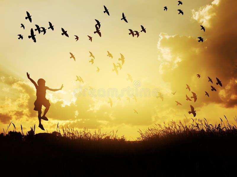 Ευτυχές παιδί που πηδά με τα πουλιά στον ουρανό ηλιοβασιλέματος στοκ εικόνες