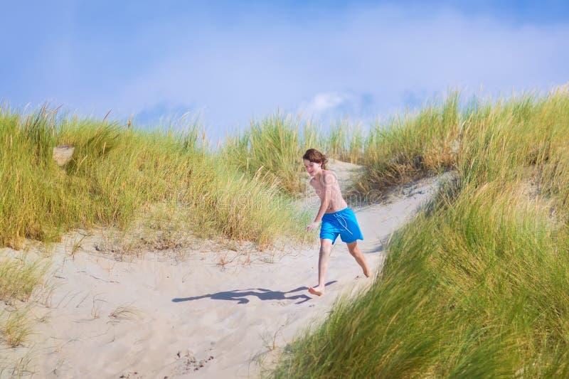 Ευτυχές παιδί που πηδά στους αμμόλοφους στοκ εικόνες