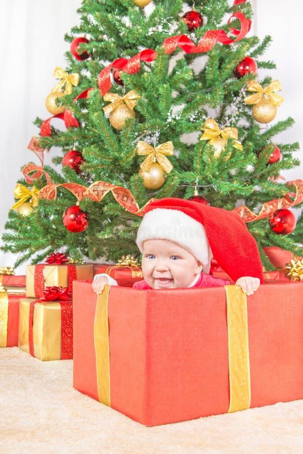 Ευτυχές παιδί στο καπέλο Χριστουγέννων στο κιβώτιο δώρων στοκ φωτογραφία
