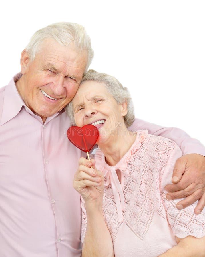 Ευτυχές παλαιό ζεύγος με την κόκκινη καρδιά-διαμορφωμένη καραμέλα στοκ εικόνα με δικαίωμα ελεύθερης χρήσης