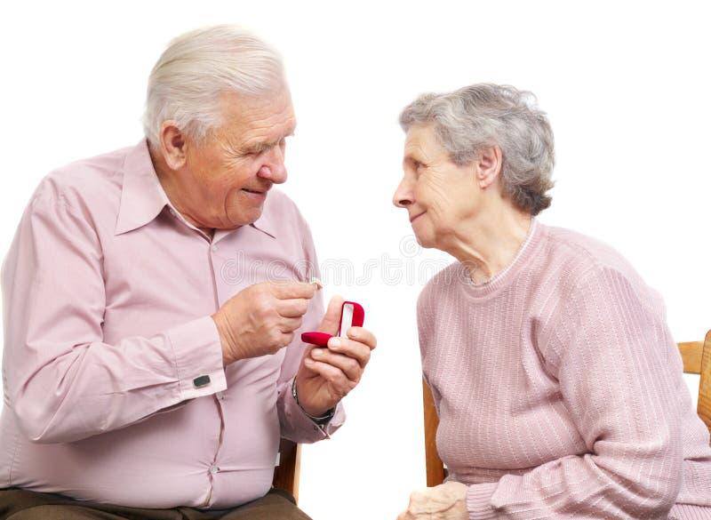 Ευτυχές παλαιό ζεύγος με το καρδιά-διαμορφωμένο δαχτυλίδι αρραβώνων στοκ εικόνα