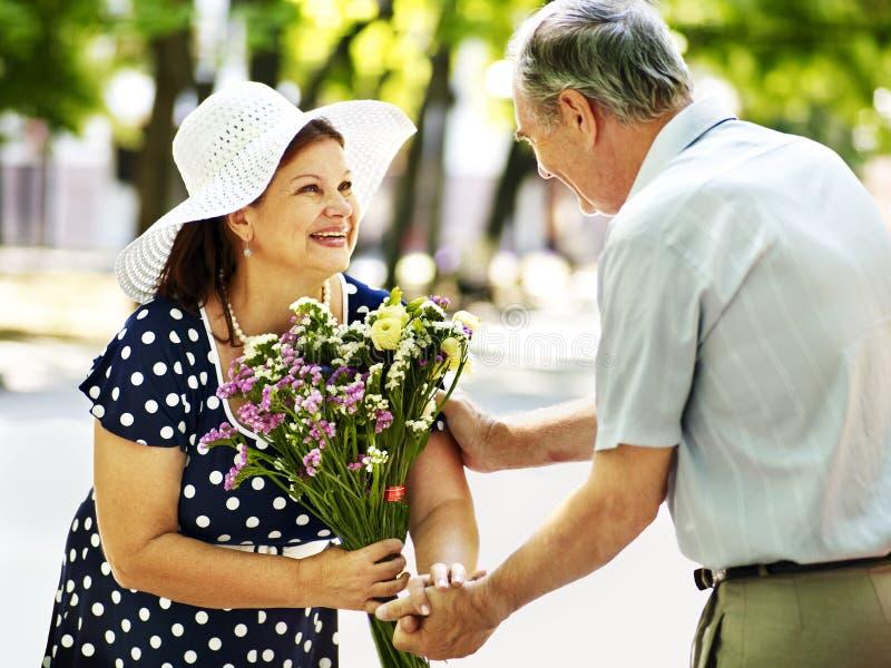 Ευτυχές παλαιό ζεύγος με το λουλούδι. στοκ εικόνες