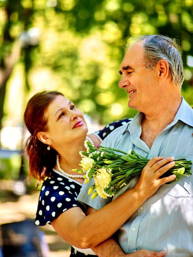 Ευτυχές παλαιό ζεύγος με το λουλούδι στοκ εικόνες