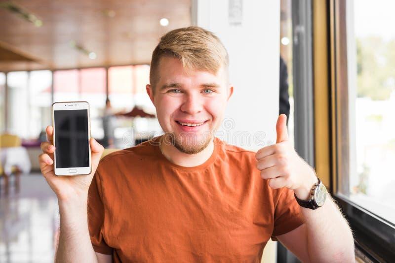 Ευτυχές περιστασιακό άτομο που παρουσιάζει την κενούς οθόνη και αντίχειρα smartphone στοκ φωτογραφία
