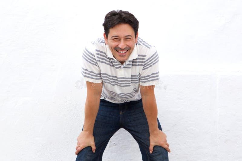 Ευτυχές περιστασιακό άτομο που στέκεται με τα χέρια στα γόνατα στο άσπρο κλίμα στοκ φωτογραφία με δικαίωμα ελεύθερης χρήσης