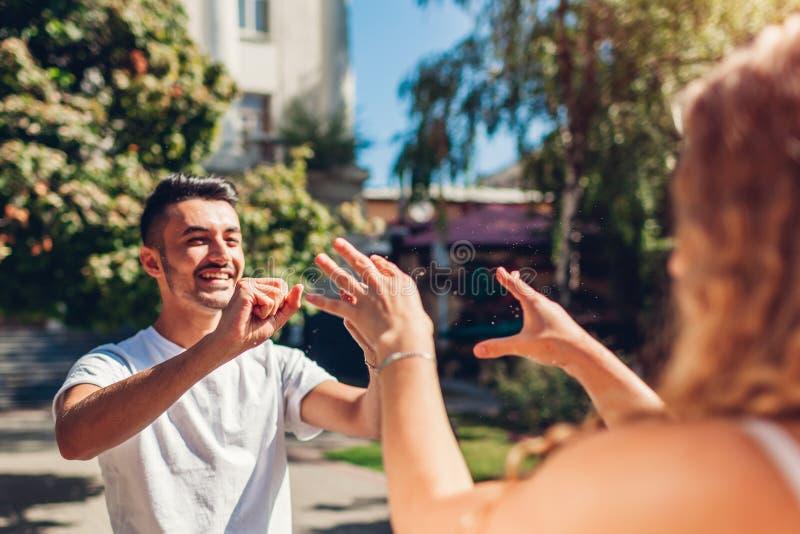 Ευτυχές πολυφυλετικό παιχνίδι ζευγών από την πηγή στην πόλη Ο άνδρας και η γυναίκα ψεκάζουν το νερό ο ένας στον άλλο στοκ φωτογραφίες