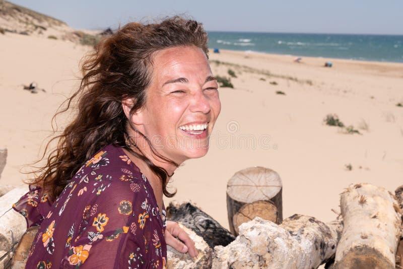 Ευτυχές πορτρέτο γυναικών στο γέλιο χαμόγελου τρίχας κυματισμού αέρα παραλιών στοκ εικόνες