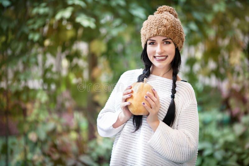 Ευτυχές πορτρέτο τρόπου ζωής μιας όμορφης νέας πρότυπης γυναίκας με μια κολοκύθα στα χέρια της στοκ φωτογραφία με δικαίωμα ελεύθερης χρήσης