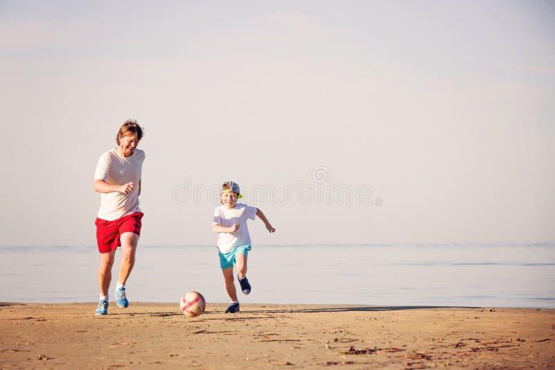 Ευτυχές ποδόσφαιρο ή ποδόσφαιρο παιχνιδιού πατέρων και γιων επάνω στοκ φωτογραφία