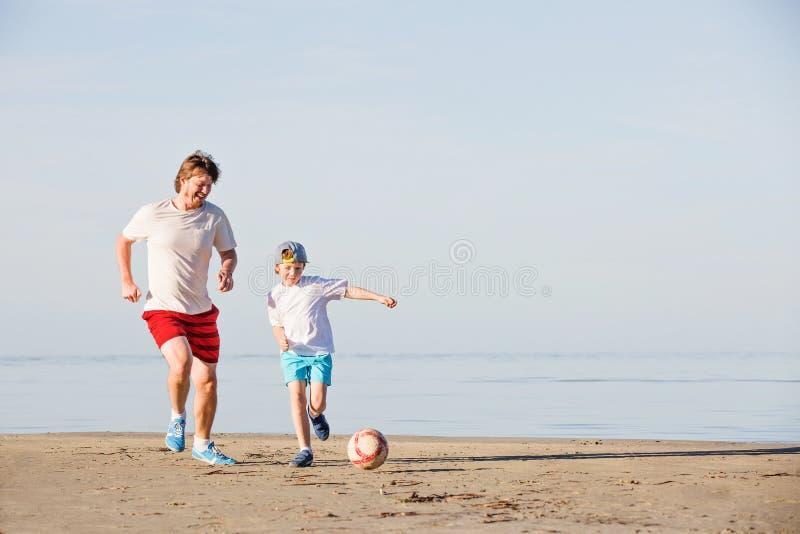 Ευτυχές ποδόσφαιρο ή ποδόσφαιρο παιχνιδιού πατέρων και γιων επάνω στοκ εικόνες