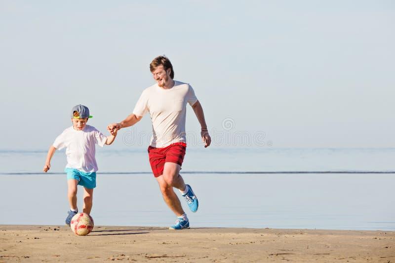 Ευτυχές ποδόσφαιρο ή ποδόσφαιρο παιχνιδιού πατέρων και γιων επάνω στοκ φωτογραφίες