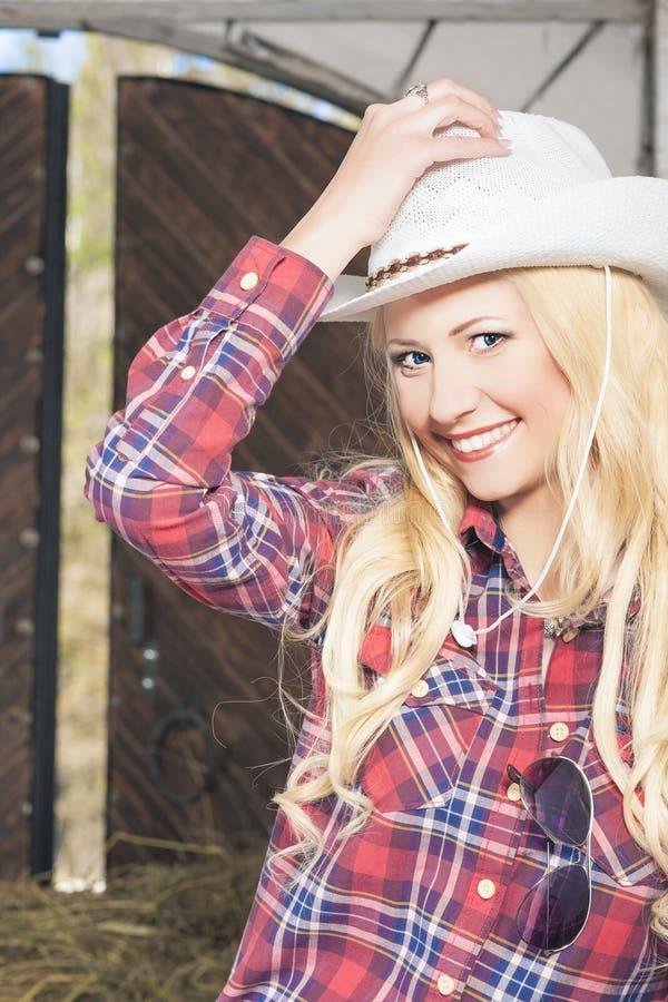 Ευτυχές προκλητικό ξανθό Cowgirl που χαμογελά μέσα του αγροτικού σπιτιού στοκ φωτογραφία