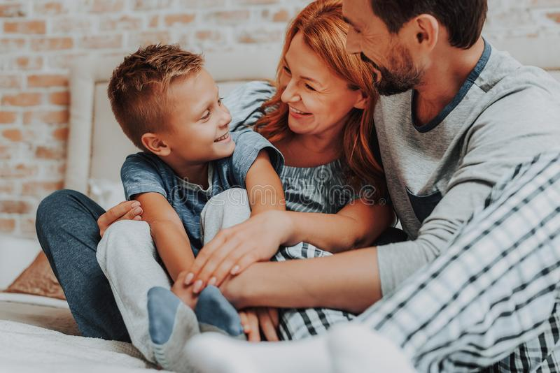 Ευτυχές πρωί με τη χαμογελώντας οικογένεια μαζί στο κρεβάτι στοκ εικόνα
