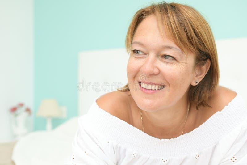 Ευτυχές πρόσωπο γυναικών κάτω και αφηρημάδα στο κρεβάτι κρεβατοκάμαρων σε ένα σαφές περιβάλλον που αντιστοιχεί σε μια Σκανδιναβικ στοκ φωτογραφία με δικαίωμα ελεύθερης χρήσης