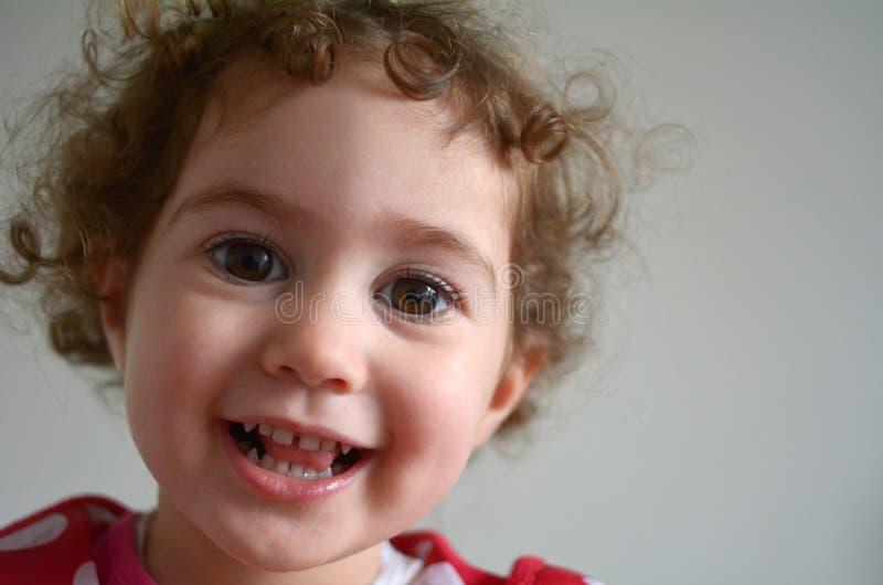 Ευτυχές πρόσωπο ενός μικρού χαμόγελου κοριτσιών στη κάμερα στοκ εικόνες