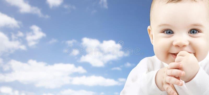 Ευτυχές πρόσωπο μωρών πέρα από το υπόβαθρο μπλε ουρανού στοκ φωτογραφία με δικαίωμα ελεύθερης χρήσης