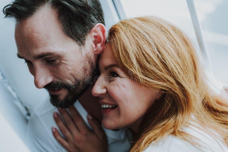 Ευτυχές ρομαντικό ζεύγος που αγκαλιάζει tenderly κοντά στο παράθυρο στοκ εικόνες